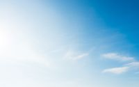 Bright and soft blue sky with small white clouds