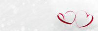 Red hearts of ribbon on white