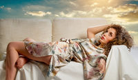 Pretty woman lying and dreaming on cloudy sky background