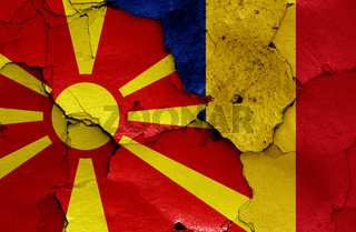 flags of North Macedonia and Romania painted on cracked wall