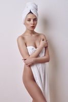 Young naked woman covering her breasts with towel