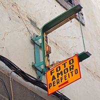a broken yellow sign above an abandoned and derelict photography shop in madeira portugal the sign reads in english, picture perfect love