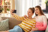 happy girls taking selfie with smartphone at home