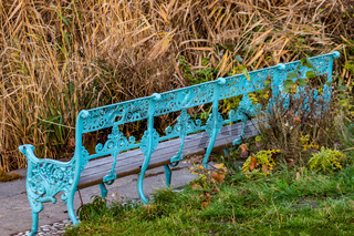 Closeup of an antique turquoise cast iron bench