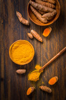 Turmeric root and powder (Curcuma longa) as cooking ingredient on wooden background