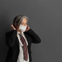 Elegant mature businesswoman putting on protective mask. Serious female office worker on gray back. Coronavirus pandemic concept