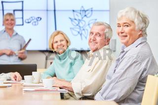 Lächelnde Senioren in einem Seminar der VHS über Heilpflanzen und Gesundheit