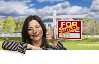 Hispanic Woman in Front of Sold For Sale Sign, House