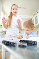 Zwei Kinder bauen Strecke aus Dominosteinen