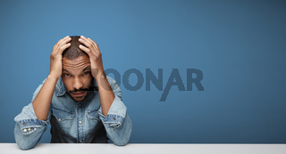Stressed African young man on blue background. Space for your text.