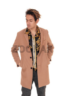 Young man standing with his beige coat in the studio
