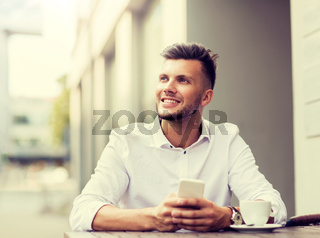 man with smartphone and coffee at city cafe