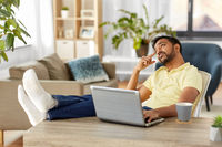 man with laptop resting feet on table at home