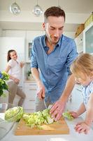 Familie bereitet Essen mit Salat vor