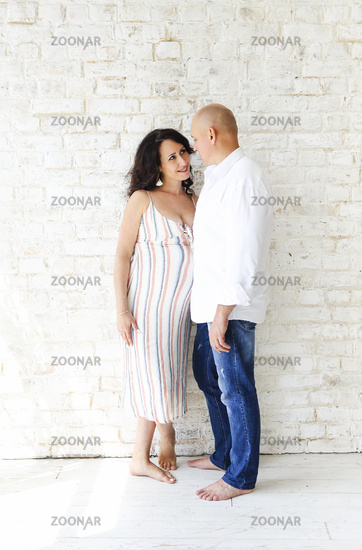 Man and pregnant woman near wall