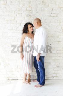 Man and pregnant woman near wall