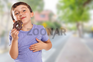 Young boy child eating donut town copyspace copy space unhealthy sweet sweets