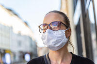 COVID-19 Pandemic Coronavirus. Young girl in city street wearing face mask protective for spreading of Coronavirus Disease 2019. Close up of young woman with medical mask on face against SARS-CoV-2