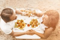 Loving mature couple have romantic date in cafe on sandy beach outdoor. Man and Woman holding hands sit at table with delicious food and drinks on sandy beach. High angle view. Toned image