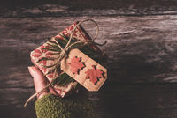 Hand holding a small secret Christmas present with creative handmade decorative rustic diy gift wrapped in red retro wrapping paper with natural vintage twine and spruce twigs as decor over old wood background giving it to someone special