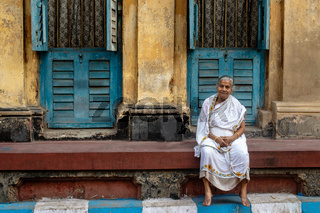 Traditionally dressed old woman sitting in front of her colorful house in the narrow streets of Calcutta.