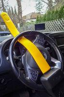 Lenkrad eines Autos mit einem gelben Lenkradschloss gesichert gegen Diebstahl