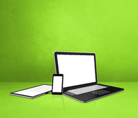 Laptop, mobile phone and digital tablet pc on green office desk