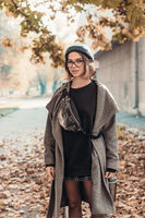Outdoor autumn portrait of young woman, walking in street of European city.