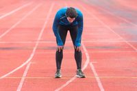 Athlete young man tired, resting on running track.