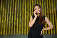 Happy young beautiful Asian businesswoman talking on the phone against bamboo fence