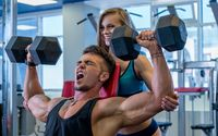 Girl helps muscular guy to exercise with dumbbells