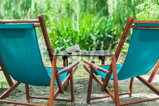 Wooden beach chairs in the garden and some books on the table. Relaxing place concept.