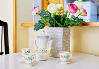 Cute teapot and cups set with floral pattern on white table beautiful persian buttercup ranunculus bunch pink white bright colors in vase no people daylight, cozy comfy living room decoration close up