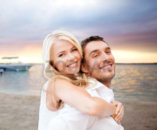 couple having fun and hugging on beach
