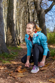 Sport. Runner. Young sportswoman stretching and preparing to run autumn