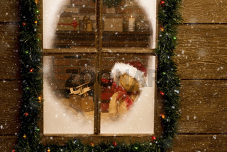 Looking through the frosty window of Santa Claus North Pole workshop with toys on work bench in front of brick fireplace. Horizontal with snow effect.