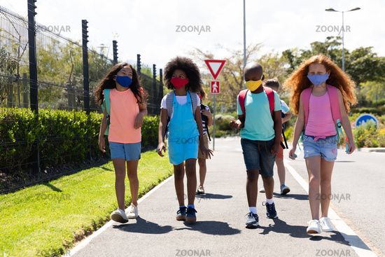 Group of kids wearing face masks walking on the road
