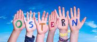 Children Hands Building Word Ostern Means Easter, Blue Sky