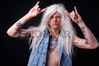 Punk rocker man wearing wig against black background