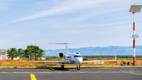 Small white private jet parked in airport