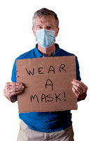 Senior man with face mask holding a cardboard sign with wear a mask message isolated against white