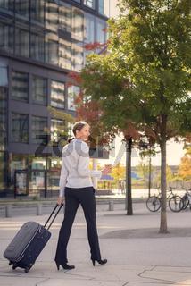 Junge Frau zieht ihren Koffer