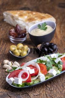 Oliven und Hummus auf dunklem Holz