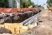 Construction works on large iron pipes at a depth of excavated trench