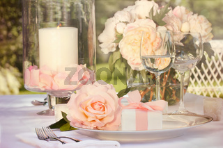 Small gift with pink rose on table