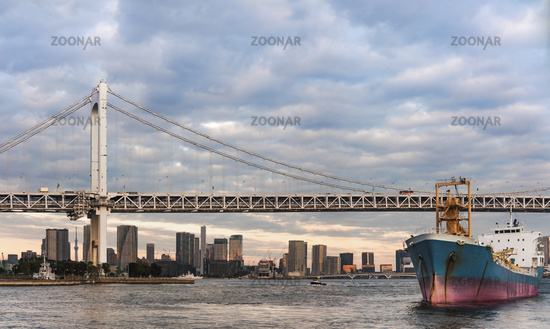 Cargo ship sailing in Odaiba Bay under the Rainbow Bridge of Odaiba bay in