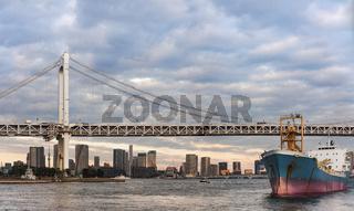 Cargo ship sailing in Odaiba Bay under the Rainbow Bridge of Odaiba bay in