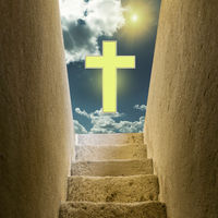 An old staircase leading from darkness to light and sky with a cross