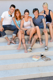 Happy college students sitting on stairs summer