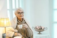 Elderly Woman Enjoys Herself At Home And Drinks Tea